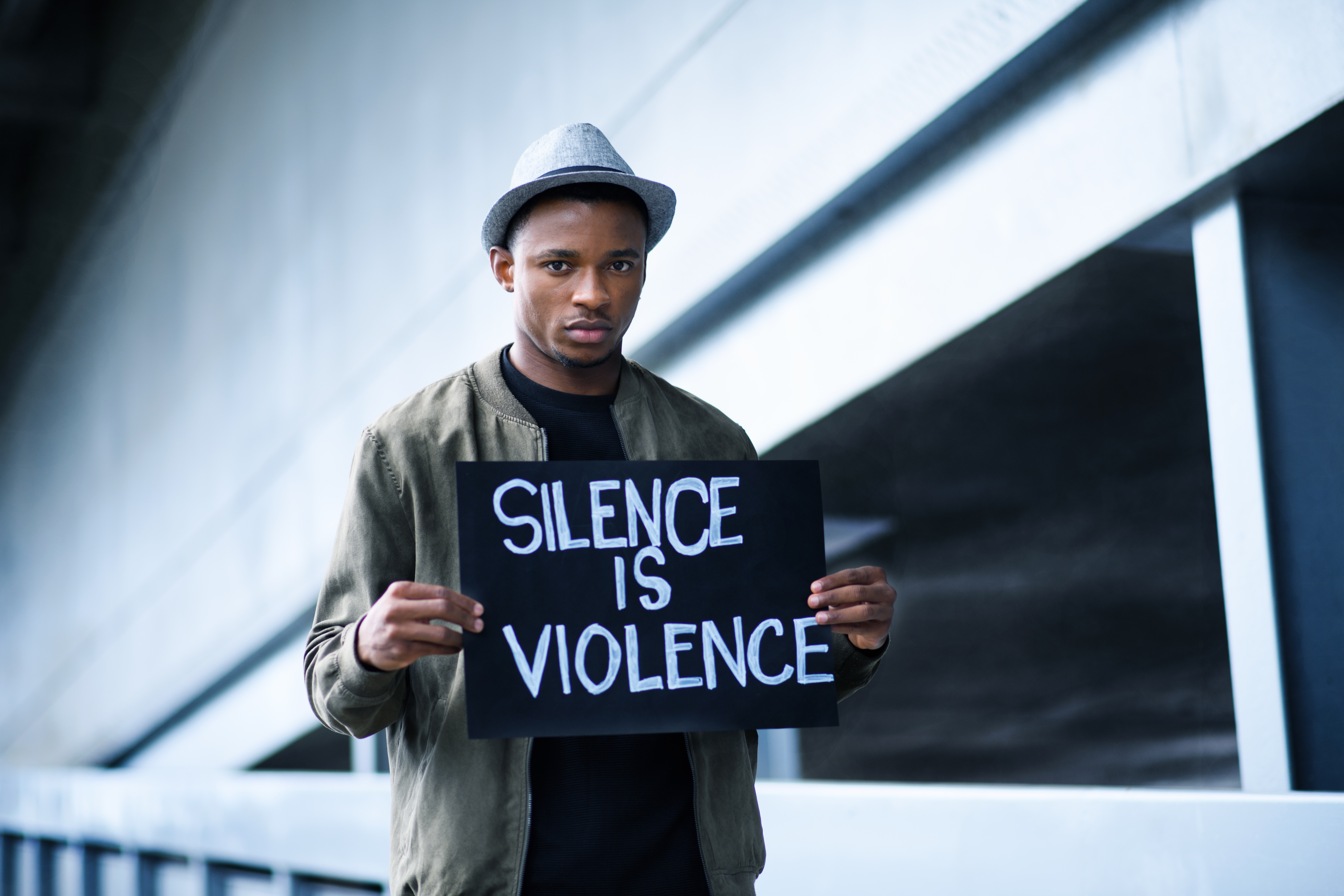 man-with-silence-is-violence-sign-standing-outdoor-4DXN7YQ