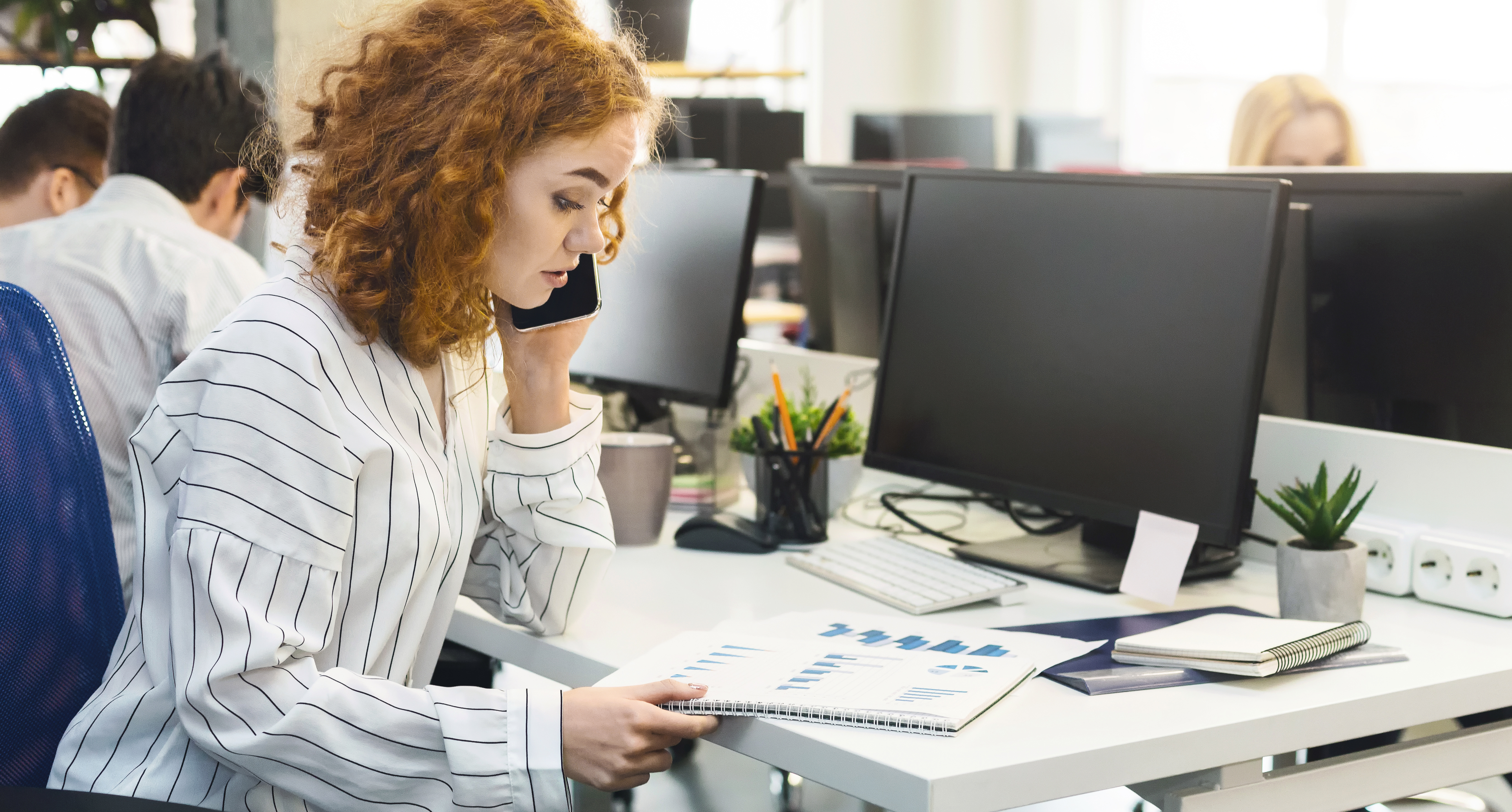 Woman looking at presentation while on the phone at a desk